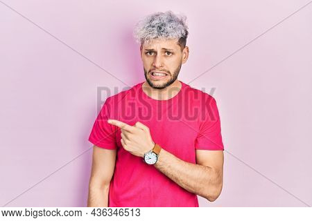Young hispanic man with modern dyed hair wearing casual pink t shirt pointing aside worried and nervous with forefinger, concerned and surprised expression