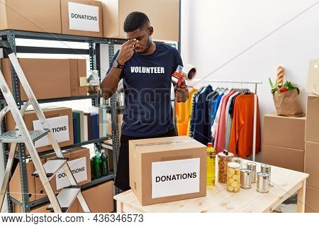 Young african american volunteer man packing donations box for charity tired rubbing nose and eyes feeling fatigue and headache. stress and frustration concept.