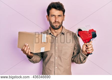 Handsome man with beard holding packing tape holding cardboard skeptic and nervous, frowning upset because of problem. negative person.