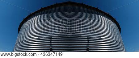 Grain Granary Silo on farm holding crops with blue sky