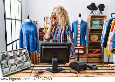 Middle age blonde woman working as manager at retail boutique shouting and screaming loud to side with hand on mouth. communication concept.