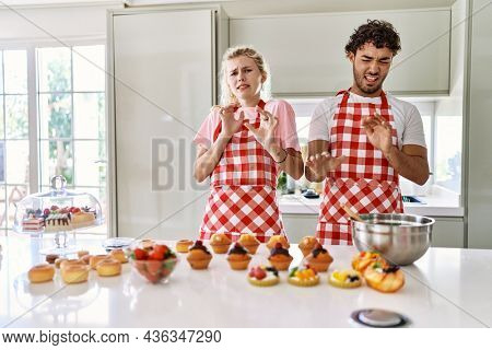 Couple of wife and husband cooking pastries at the kitchen disgusted expression, displeased and fearful doing disgust face because aversion reaction. with hands raised