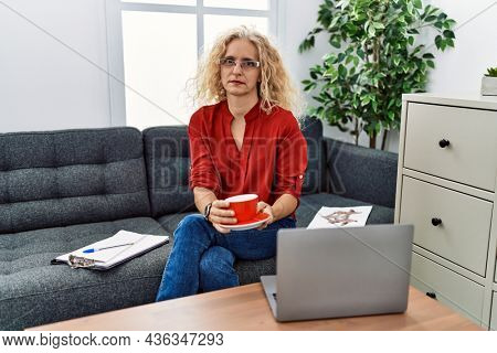Middle age psychologist woman at consultation office relaxed with serious expression on face. simple and natural looking at the camera.