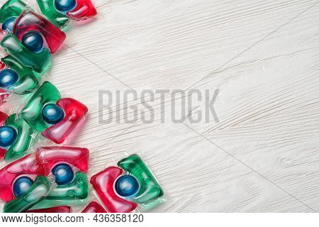 Pile Of Washing Gel Capsule Pods With Laundry Detergent On White Wooden Table.