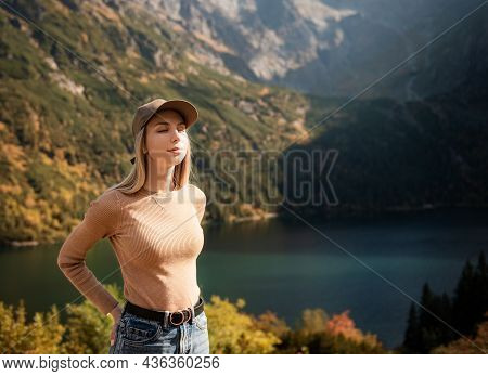 Wanderlust And Travel Concept. Stylish Traveler Girl In Cap Looking At Mountains, Exploring Woods. Y