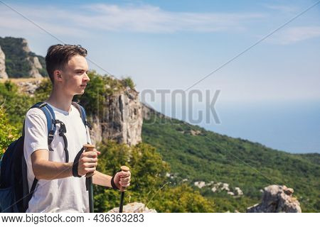 Teenager boy holding trekking poles standing on the top of a cliff gazing to the valley below enjoying a view