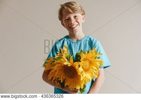 Portrait of a happy smiling casual preteen boy in t-shirt standing over isolated gray wall background holding sunflower bouquet