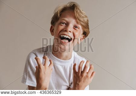 Portrait of a happy excited casual preteen boy in t-shirt standing over isolated gray wall background