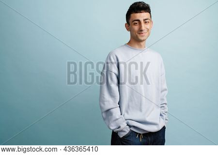 Young middle eastern man smiling and looking at camera isolated over blue background