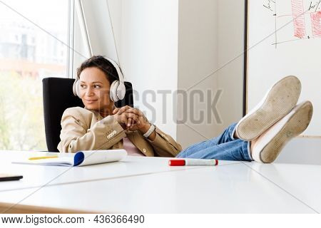Middle eastern woman listening music with headphones while working at office