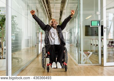 Middle eastern man making winner gesture while sitting in wheelchair at office