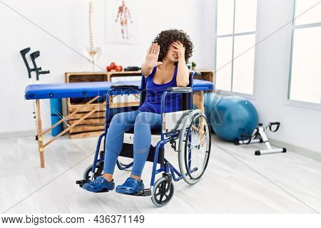 Young middle eastern woman sitting on wheelchair at physiotherapy clinic covering eyes with hands and doing stop gesture with sad and fear expression. embarrassed and negative concept.
