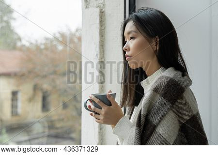 Young Sad Asian Woman Drinks Coffee Or Tea And Looks Out The Window Covered With A Blanket