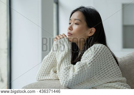 A Young Unhappy Asian Woman Sitting On The Couch With A Sad Face And Looking Out The Window.
