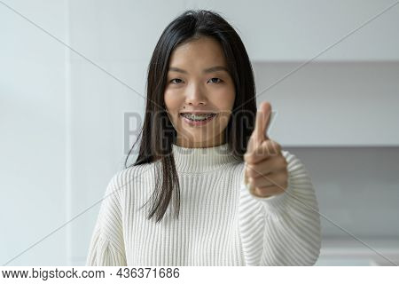 Asian Woman Smiles And Gives A Thumbs Up To The Camera