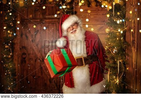 Happy Santa Claus stands in a wooden house holding out a Christmas gift with a happy smile. Merry Christmas and Happy New Year!
