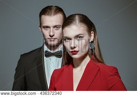 Stunning beautiful couple of young people in elegant pantsuits on a gray background in the studio. Impeccable look. Evening fashion.