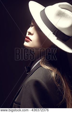 Fashion shot. Attractive model girl in a strict black pantsuit and white hat poses on a black studio background.