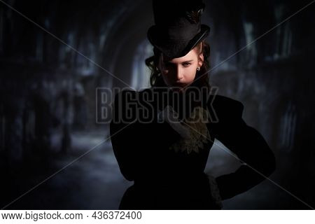 Mysterious beautiful lady dressed in strict black clothes of the 19th century looks suspiciously into the darkness of the old dark castle. 19th - early 20th century style. Horror, thriller.