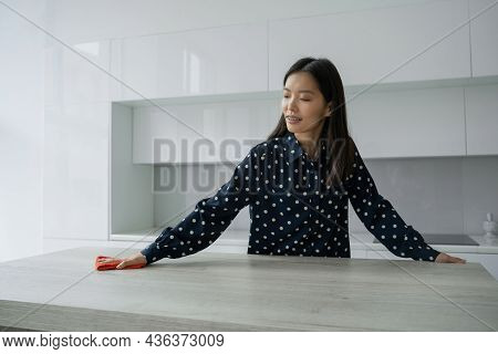 Asian Woman Cleans And Wipes The Table With A Microfiber Cloth In The Kitchen. A Woman Does Househol