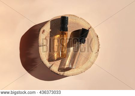 Two Glass Perfume Samples On A Wooden Tree Tray Lying On A Beige Background. Luxury And Natural Cosm