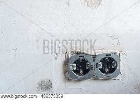 Open Electrical Outlets On A Grungy Gray Wall