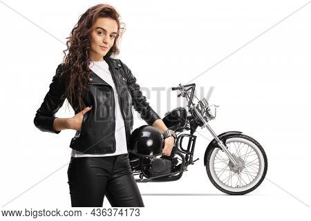Young female biker in a leather jacket holding a helmet and standing in front of a chopper isolated on white background