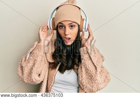 Young hispanic woman listening to music using headphones in shock face, looking skeptical and sarcastic, surprised with open mouth