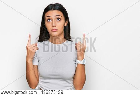 Young hispanic girl wearing casual white t shirt pointing up looking sad and upset, indicating direction with fingers, unhappy and depressed.