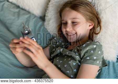 Portrait of preteen beautiful blond hair girl lying in the bed with clock. Female kid schoolgirl smiling in the bedroom