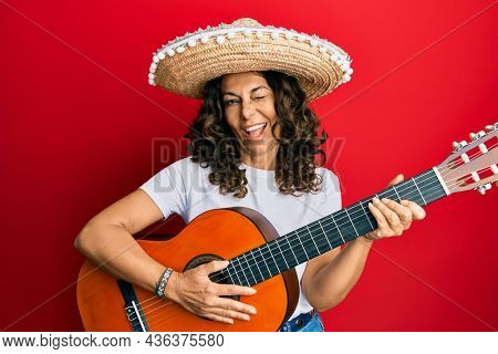 Middle age hispanic woman holding mexican hat playing classical guitar winking looking at the camera with sexy expression, cheerful and happy face.