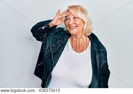 Middle age blonde woman wearing leather jacket very happy and smiling looking far away with hand over head. searching concept.