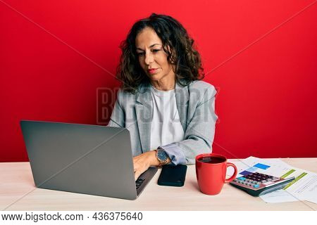 Beautiful middle age woman working at the office drinking a cup of coffee relaxed with serious expression on face. simple and natural looking at the camera.