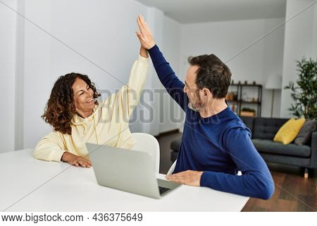 Middle age hispanic couple smiling happy high five. Sitting on the table using laptop at home.