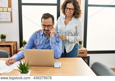Two middle age business workers smiling happy flirting at the office.