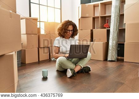 Middle age hispanic woman sitting on the floor at new home with laptop thinking attitude and sober expression looking self confident