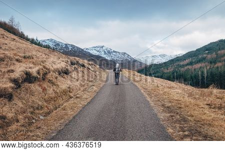Lonely Backpacker Man Walking With Backpack By Scottish Highlands Mountain Road With Snowy Peaks At