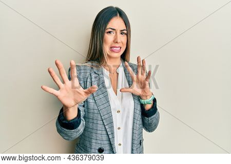 Young hispanic woman wearing business clothes disgusted expression, displeased and fearful doing disgust face because aversion reaction. with hands raised