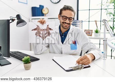 Handsome hispanic man working as psychologist showing rorschach test at professional clinic
