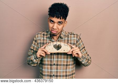 Young african american man holding bread loaf with heart shape depressed and worry for distress, crying angry and afraid. sad expression.
