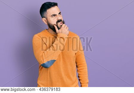 Hispanic man with beard wearing casual winter sweater thinking worried about a question, concerned and nervous with hand on chin