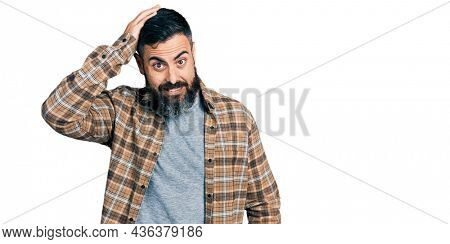 Hispanic man with beard wearing casual shirt confuse and wonder about question. uncertain with doubt, thinking with hand on head. pensive concept.