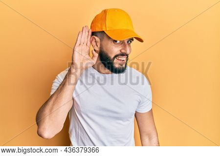 Young man with beard wearing yellow cap smiling with hand over ear listening and hearing to rumor or gossip. deafness concept.