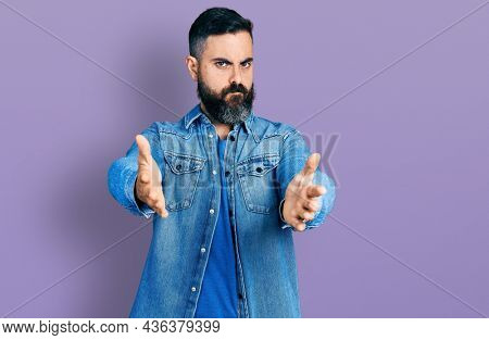 Hispanic man with beard with open arms doing hug gesture skeptic and nervous, frowning upset because of problem. negative person.