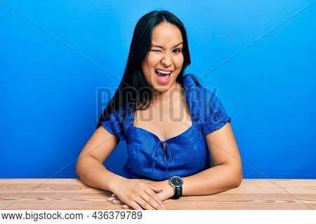 Beautiful hispanic woman with nose piercing sitting on the table winking looking at the camera with sexy expression, cheerful and happy face.