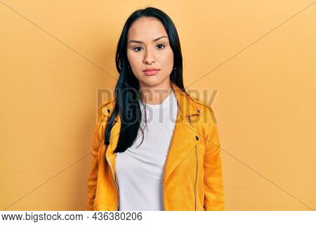 Beautiful hispanic woman with nose piercing wearing yellow leather jacket relaxed with serious expression on face. simple and natural looking at the camera.