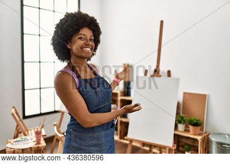 Young african american woman with afro hair at art studio inviting to enter smiling natural with open hand