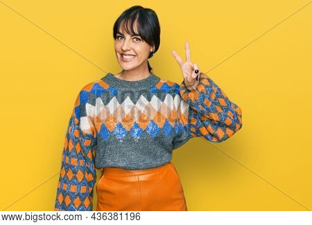Young hispanic woman wearing casual clothes smiling with happy face winking at the camera doing victory sign. number two.