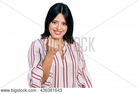 Young hispanic girl wearing casual clothes beckoning come here gesture with hand inviting welcoming happy and smiling