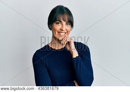 Young hispanic woman wearing casual clothes smiling looking confident at the camera with crossed arms and hand on chin. thinking positive.